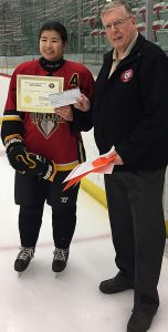 Bob Green of the Friends of Alberta Junior Hockey Society presents Elizabeth Wong with her scholarship.