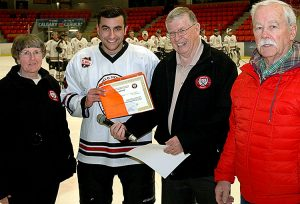 Kieran Lamont of the Calgary Jr. B Blackhawks is presented with the Nickerson Family Memorial Scholarship. From left to right are Jean Green (Friends of AJH society), Kieran Lamont, Bob Green (Friends of AJH Society), and Don Speers (Friends of AJH Society).