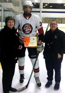 Jean Green of the Friends of AJH Society (left) and Cathy Hosowich, the Governor for Jr. C division of Hockey Calgary (right), present Shawn Stephen with a Friends of Alberta Junior Hockey Society Scholarship.