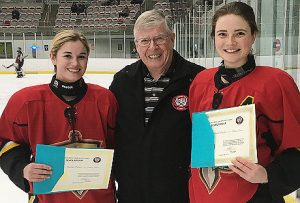 Jocelyn Prince and Libby Wheeler of the Calgary titans, winners of a 2018 Friends of Alberta Junior Hockey Society Scholarships are presented with their scholarships by Bob Green from the Friends of AJH Society.