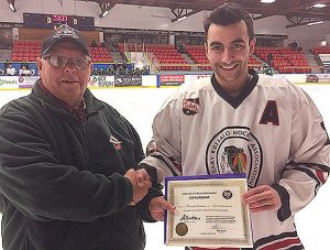 Don Allan of the Friends of Alberta Junior Hockey presents Charles S. Noble Scholarship winner Kieran Lamont with his scholarship