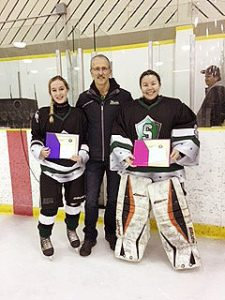 Glenn Ball from the Friends of Alberta Junior Hockey Society presents Kendelle Perneel(L) and Hailey Kucher(R) with their Friends of Alberta Junior Hockey Society scholarships