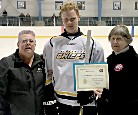 Julien Bergeron of the Calgary Blackfoot Jr. C receiving a Friends of Alberta Junior Hockey Society Scholarship. Presenting are Jean Green on the right of the Friends and Cathy Hosowich of Hockey Calgary on the left