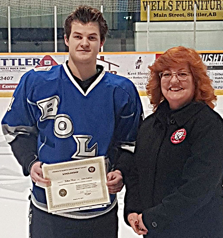 Ethan Rost of the Stettler Lightning receivies a Friends of Alberta Junior Hockey Society scholarship from Donna Williams of the Friends Society.