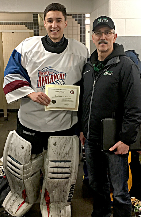 Jack Holan of the Edmonton Avalanche receives a Friends of Alberta Junior Hockey Society scholarship from Glenn Ball of the Friends of Alberta Junior Hockey Society.