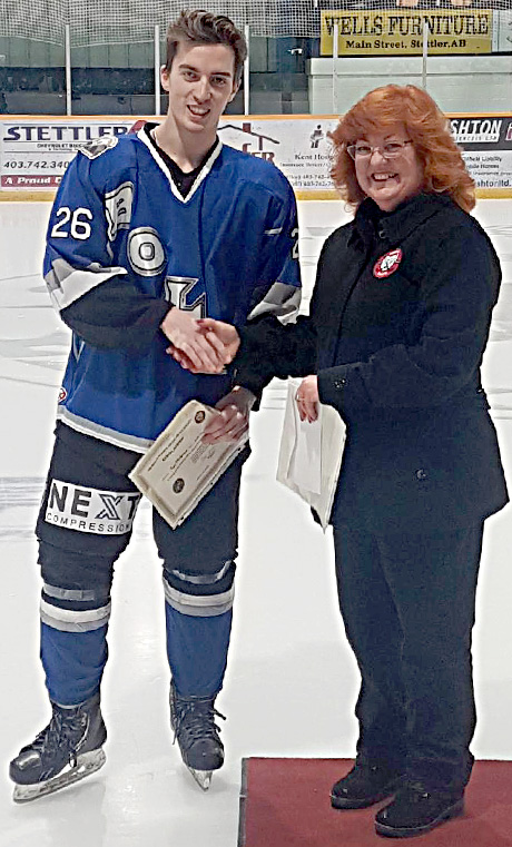 Tye Mulgrove of the Stettler Lightning receives a Friends of Alberta Junior Hockey Society scholarship from Donna Williams of the Friends Society.
